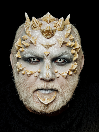 creepy alien: Alien or reptilian makeup. Demon head on black background. Man with dragon skin and beard. Horror and fantasy concept. Monster face with white eyes, sharp thorns and warts.