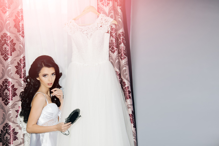 Bride with long brunette hair. Wedding holiday celebration. Girl with fashionable makeup look at mirror. Beauty and fashion. Woman with beautiful dress Stock Photo