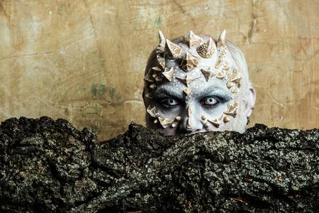 머리에 뿔 고블린입니다. 날카로운 가시와 사마귀가있는 괴물. 드래곤 피부와 수염 난 얼굴을 가진 남자. 베이지 색 벽에 오래 된 나무 껍질 뒤에 사제. 스톡 콘텐츠