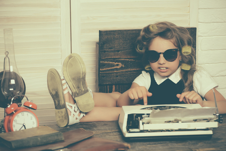 Small girl with curler in hair. Kid choose career in glasses. Education and childhood. Child with briefcase and alarm clock. Little baby secretary.