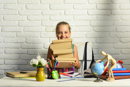 Girl near flowers, globe and colorful stationery on her desk. Schoolgirl with happy face holds big pile of books. Kid and school supplies on white brick background. Back to school and homework concept
