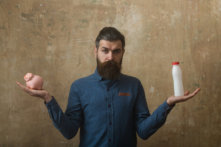 man with long beard hold money box and plasic bottle in hand on beige background