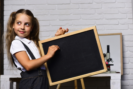 Schoolgirl with cunning face holds small blackboard. Kid and school supplies on white brick background. Girl in her classroom or laboratory. Back to school and happy childhood concept