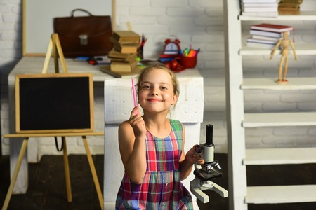 Girl with smiling face in front of desk with school supplies, shelf and blackboard. Schoolgirl holds microscope and pink pencil on study room background. Kid does experiments. Back to school concept