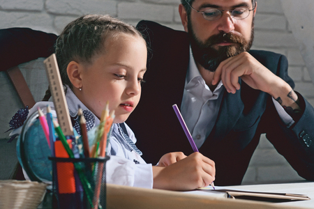 Kid and man sit by desk with school supplies. Schoolgirl and her dad with serious faces do homework. Girl and father in classroom on white brick background. Back to school and home schooling concept photo
