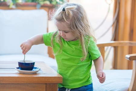 Little kid boy making tea. Childhood and baby care concept. Boy child mixing sugar in blue cup. Child boy with blond long hair mixing sugar with teaspoon. Healthy breakfast for child.