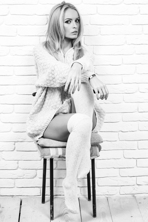 girl or beautiful cute woman fashion model with blond hair in sexy knitted sweater sits on chair on brick wall, black and white