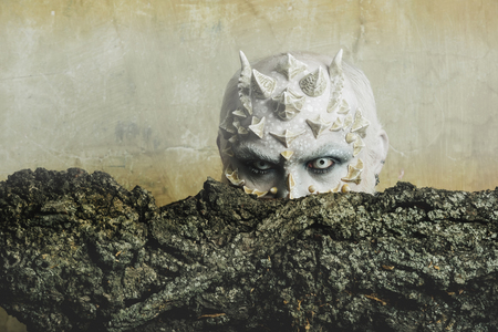 Tree spirit and fantasy concept. Goblin with horns on head. Monster with sharp thorns and warts. Druid behind old bark on beige wall. Man with dragon skin and bearded face.
