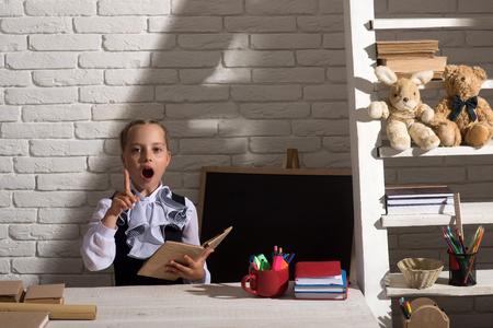 Schoolgirl has idea holding open book near blackboard and bookshelf, copy space. Kid in uniform on white brick background. Girl sits at desk with colorful stationery. Classroom and study time concept Reklamní fotografie