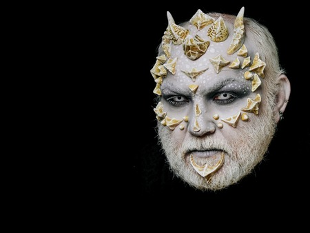 horror man or monster with horns or thorns on face with futuristic makeup of guy alien with beard and lens in eyes isolated on black background, copy space Stock Photo