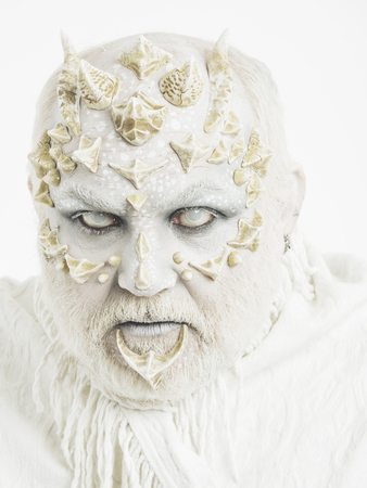 Reptilian man with blind eyes and grey beard on thorny skin face on white background. Mystery and fantasy concept. Фото со стока