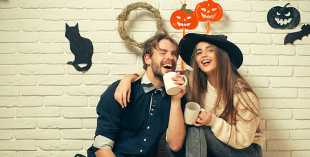 Halloween woman with long hair in witch hat. Happy couple in love with cups smiling. Man in casual wear sitting on floor. Holiday traditional symbols on white brick wall. Celebration and party concept