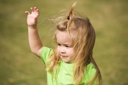 かわいい笑顔で少年の小さな子供に直面する自然な草の背景に手を振っている緑のシャツに金髪長い髪
