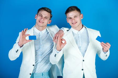 男性 ok のジェスチャーで空白のカードを保持します。ビジネス コミュニケーションと会議。ビジネスマンの笑顔で白いジャケットのブルーの背景。