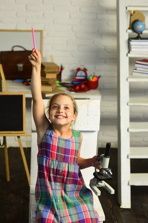 Girl with happy face in front of desk with school supplies, bookshelf and board. Schoolgirl holds microscope and pink pencil up on study room background. Back to school concept. Kid does experiment