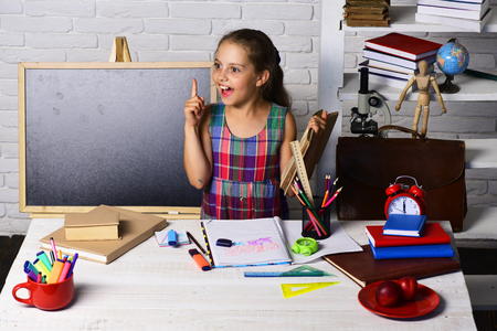 Back to school concept. Schoolgirl having new idea holds open book. Girl near pile of books, red clock, schoolbag and colorful stationery on her desk. Kid and school supplies on classroom background