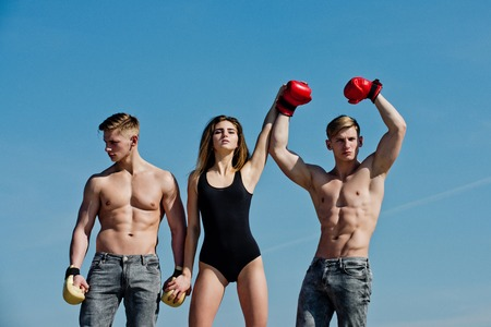 Boxer workout and healthy fitness. Woman and twins with muscular body. Sport people or team work. Men and coach sunny outdoor on blue sky. Winner and loser in boxing gloves with girl. Imagens