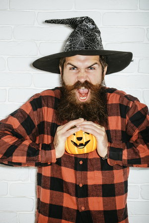 Halloween hipster with beard shouting in wizard hat. Trick or treat. Jack o lantern. Holiday celebration concept. Man with pumpkin on white brick wall. photo