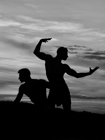 silhouette of men or bodybuilders, athlete people with sexy torso outdoor in sunset sky, black and white Stock Photo - 84339205