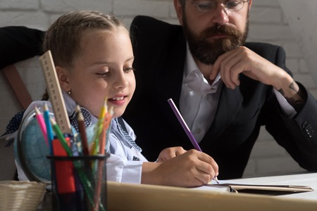 Family sits by desk with school supplies. Classroom and home education concept. Schoolgirl and her dad with busy faces write in notebook. Girl and her father in study room on white brick background photo