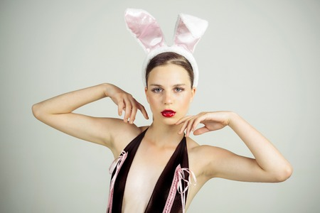 Woman with red lips wearing rabbit ears. Easter holiday concept. Playboy girl posing on grey background. Sexy bunny model. Stock Photo