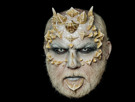 Horror and fantasy concept. Man with dragon skin and beard. Monster face with white eyes, sharp thorns and warts. Demon head isolated on black. Alien or reptilian makeup.