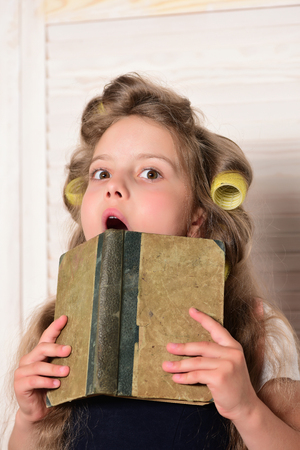 Little baby with book. Child in school. Education and childhood. Small girl with curler in hair. Banco de Imagens