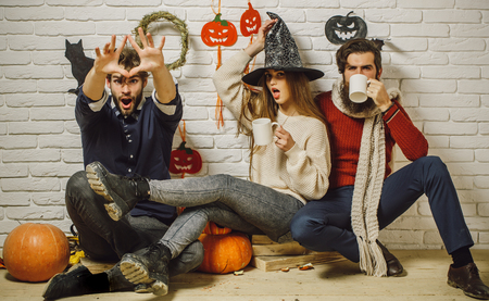 Halloween friends surprised drinking tea and celebrating. Holiday traditional symbols on white brick wall. Girl in witch hat. Men in casual wear sitting on floor. Friendship and people concept. photo