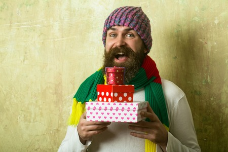 Holiday celebration and shopping. Christmas and birthday. Hipster with present box in hat. Guy with happy face and gift pack. Man with long beard in colorful scarf. photo