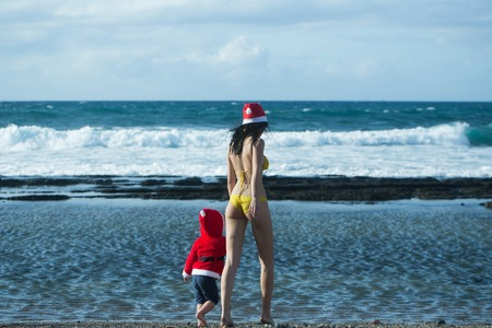 Christmas and new year celebration. Woman and child walking on sea beach. Mothers day and family love. Girl in swim suit and boy wearing santa costume. Winter holidays concept. Imagens - 84269996