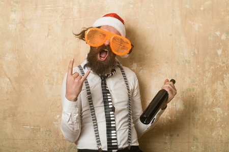 New year guy with in hat. Holiday and celebration. Santa claus man with wine bottle. Party and alcohol drink. Christmas man with happy face in glasses. Stock Photo