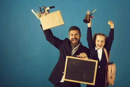 Kid and tutor hold school supplies and blackboard. Girl in uniform and bearded man in suit. Teacher and schoolgirl with cheerful faces on blue background. Classroom and alternative education concept Stock Photo