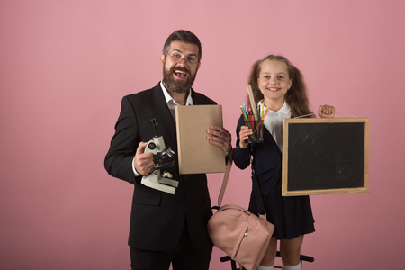 Father and schoolgirl with happy faces on pink background. Kid and dad hold microscope, book, stationery and blackboard. Man and girl in school uniform. Home schooling and back to school concept