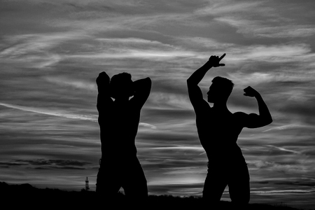 men or bodybuilders silhouettes, athlete people with sexy torso outdoor in sunset sky, black and white Stock Photo - 84350230
