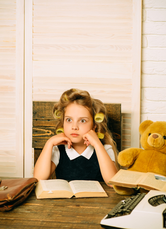 Education and childhood. Little baby secretary in cabinet with bear. Kid reading book. Child play in school. Small girl with curler in hair.