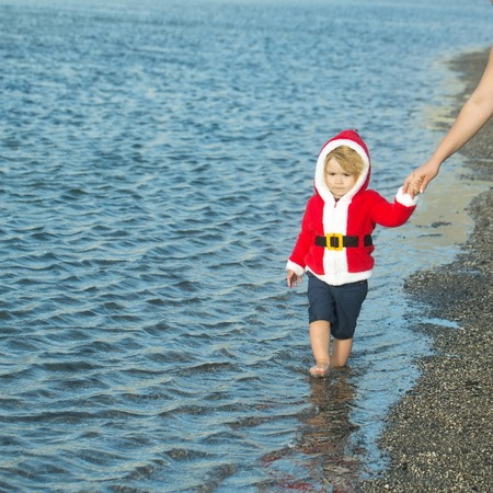Boy in santa costume walking on sea beach. Child holding female hand. Mothers day and family love. Christmas and new year. Winter holidays celebration concept. Imagens - 84375008