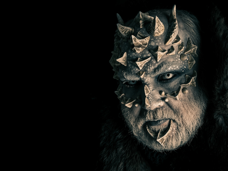 Horror and fantasy concept. Monster with sharp thorns and warts on face. Man with dragon skin and grey beard. Demon head isolated on black. Alien or reptilian makeup, copy space Stock Photo