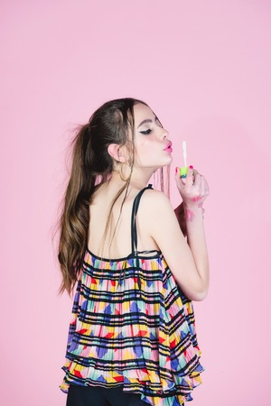 woman with fashionable makeup and hair blow in bubble blower on pink studio background