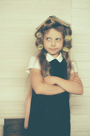 Child in school. Little baby with book. Education and childhood. Small girl with curler in hair. Stock fotó