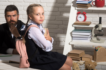 Schoolgirl and her dad with serious faces hold book and glasses. Classroom and home education concept. Man and girl sit at desk with school supplies. Daughter and her father on white brick background photo