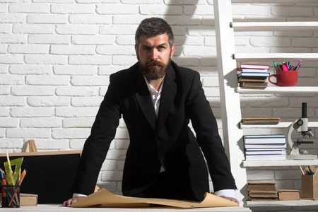 Professor with serious face expression stands by desk with paper. Man with beard on white brick wall background. Teacher and school supplies in classroom. Classic education and knowledge concept photo
