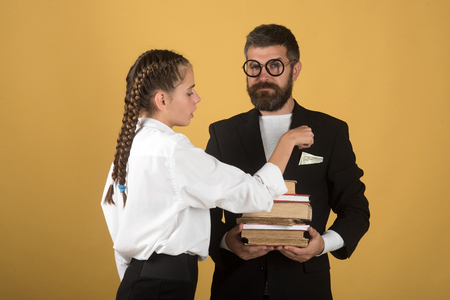 Father and schoolgirl with serious faces on yellow background. Teenager takes pocket money and dad holds pile of books. Education and back to school concept. Girl with braids and man with glasses photo