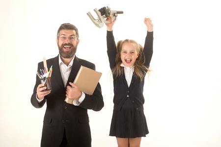Father and schoolgirl with happy faces isolated on white background. Kid and dad hold microscope, book and stationery. Girl and man in suit and school uniform. Home schooling or back to school concept photo