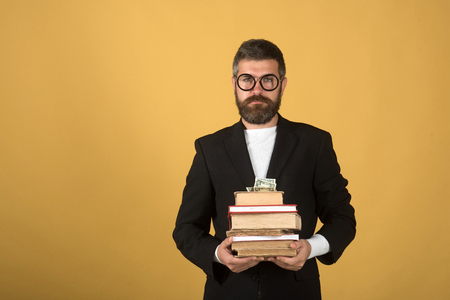 Teacher holds pile of books and money. Professor with serious face expression. Teaching and knowledge concept. Man with beard on yellow background, copy space photo