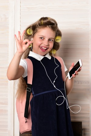 Kid choose career and listen music. Education and childhood. Child with headset and phone. Small girl with curler in hair.