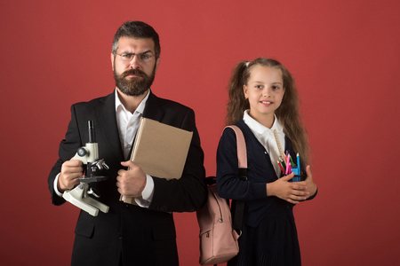 Kid and tutor hold microscope, book and stationery. Teacher and schoolgirl with strict and smiling faces on terracotta background. Education and back to school concept. Girl with bag and man in suit photo