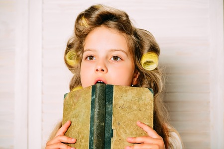 Child in school. Little baby with book. Education and childhood. Small girl with curler in hair. Banco de Imagens