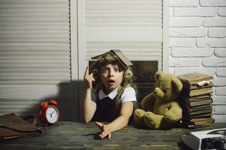 child or small girl with curler in hair with briefcase, retro typewriter, alarm clock and bear on table in secretary or business cabinet