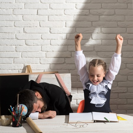 Schoolgirl with positive emotions and her sleeping tutor. Back to school and tiring homework concept. Girl and teacher in classroom on white brick background. Man and kid at desk with school supplies Stock fotó
