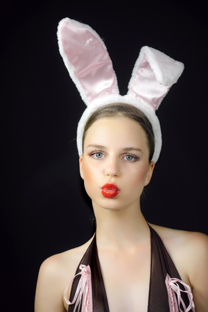 Woman with duck face wearing rabbit ears. Sexy bunny model. Playboy girl posing on black background. Easter holiday concept.